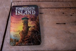 Forbidden Island game review- photo of a Forbidden Island game box cover on a wooden table top.